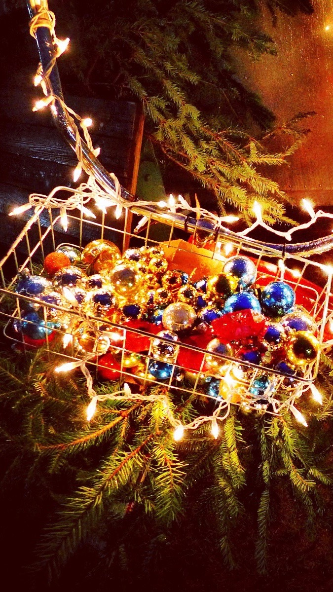 Sparkle and glow! Christmas wallpaper for iPhone 7. Glittering ornaments in a bicycle basket with lights and evergreens. Sparkly and festive!