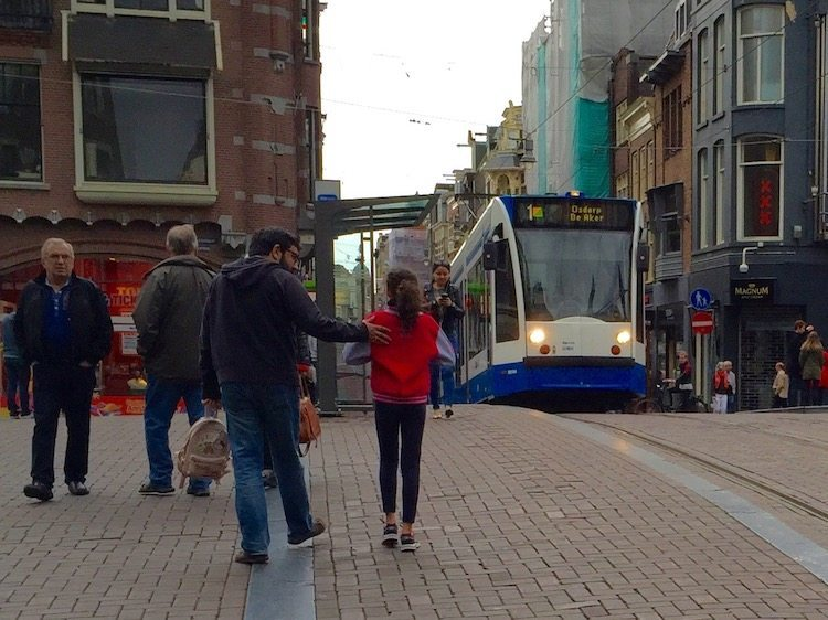 City street in Amsterdam with tram on an Eating Amsterdam Dutch food tour.