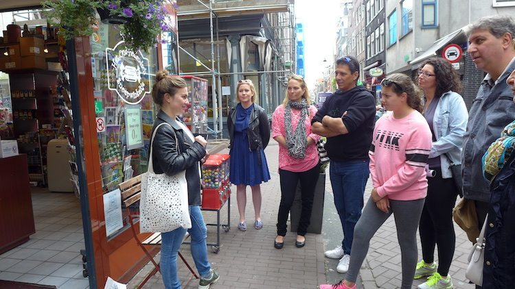 Tour group gathered on the sidewalk on an Eating Amsterdam Dutch food tour