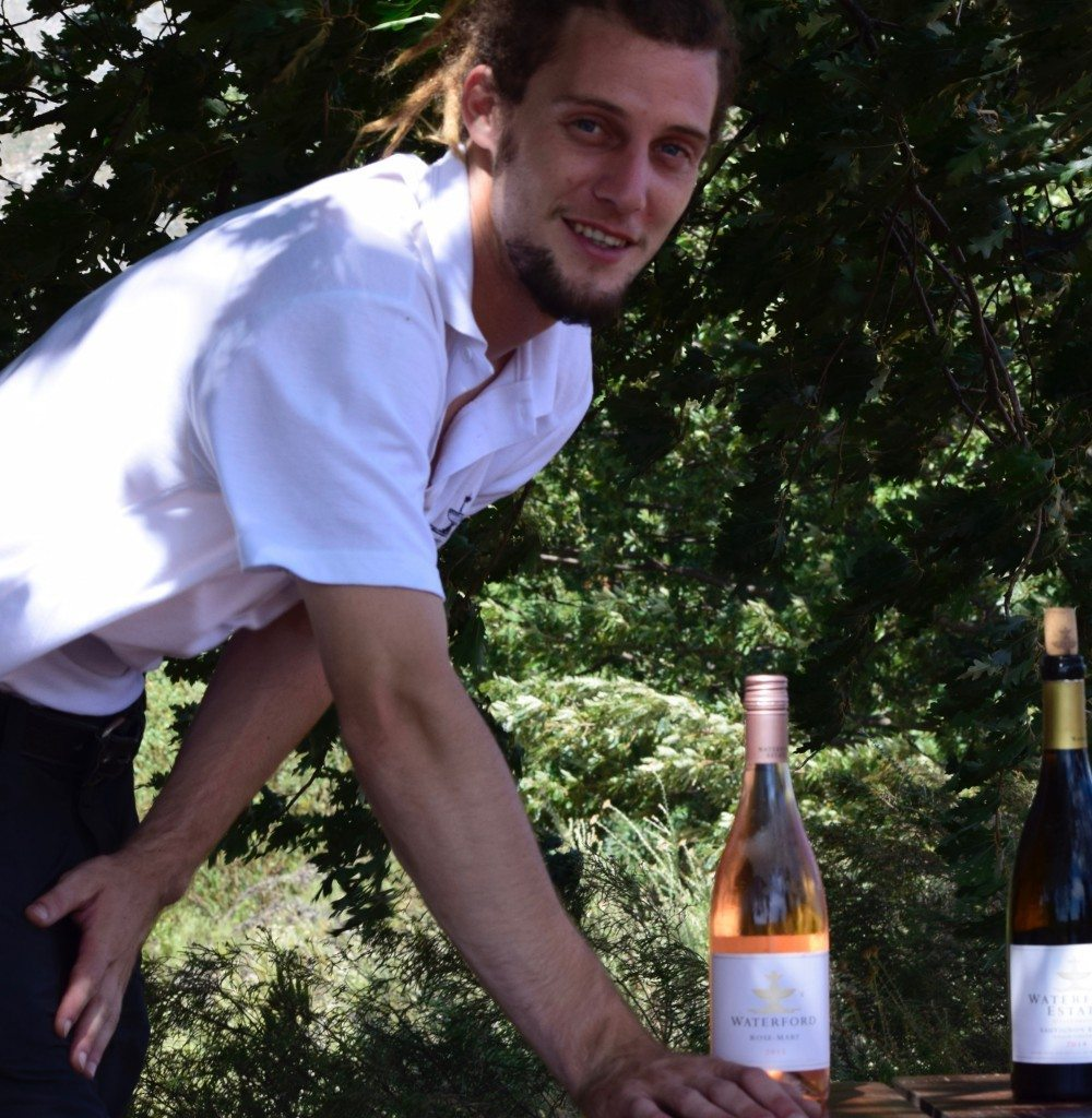 Young man serving wine in vineyard in Stellenbosch, home of South Africa wine tour