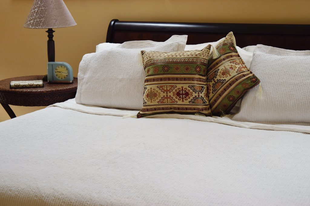 White linens in a bedroom makeover help to cure your wanderlust by making you think you're in a beach villa.
