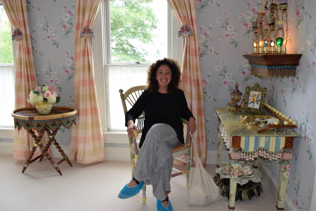 woman in Mackenzie-Childs farmhouse bedroom