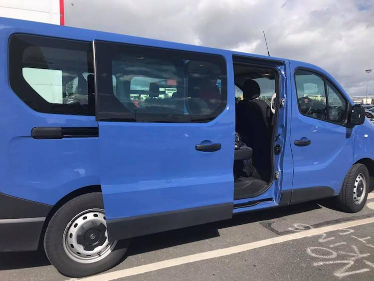 Large blue passenger rental van that you can reserve with AutoSlash and save money