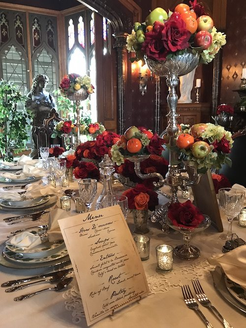setting a formal dining table with large floral and fruit arrangements at Lyndhurst Mansion in Tarrytown