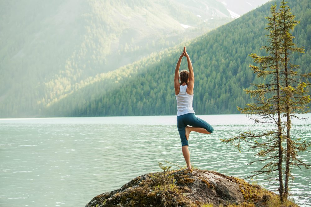 young woman doing tree pose by a lake, a yoga move for beginners
